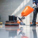 person scrubbing floor using black and orange machine