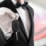 man in black suit jacket holding car key
